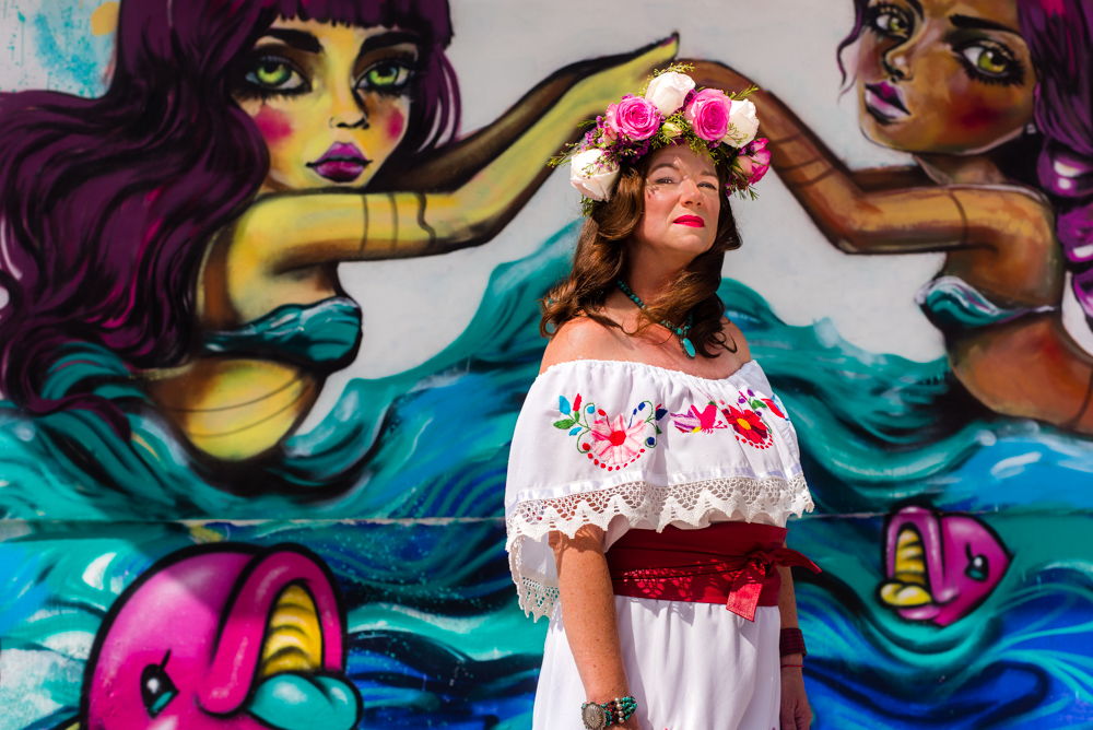 Angela Martinez-Mainberger stands in a white off the shoulder dress with floral highlights and a red belt-sash. She is wearing red and pink blossoming flowers in a wreath on her head. She is standing underneath a mural of two women in the sea, possible mermaids, resting their hands on top of her head while gazing at the camera.