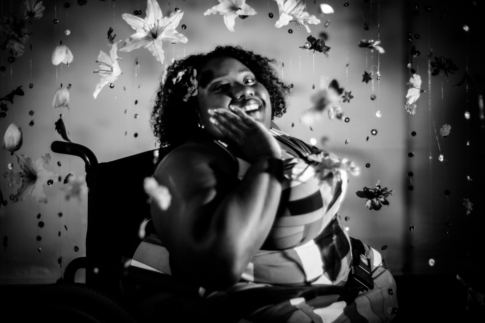 In a black and white photo, Belinda Senatus sits in her chair smiling, resting her cheek on her hand. She is surrounded by numerous hanging and floating flowers.