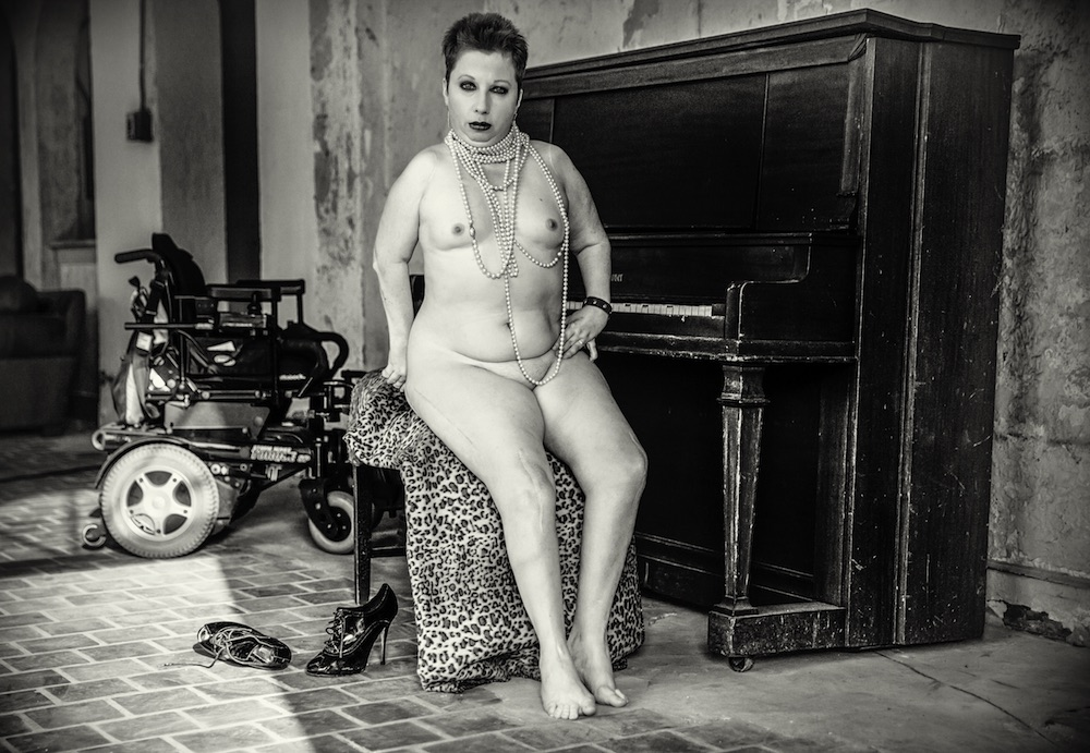 Heidi sits bolds, and very much completely naked, on a worn bench in front of a beaten piano. Heidi is loosely draped in pearls and he left hand is resting on her hip. She is gazing directly at the camera, and her dark makeup emphasizes her features. She is sitting on a leopard print fur jacket. There are stiletto boots on the floor to her right. Her electric wheelchair is in the background.